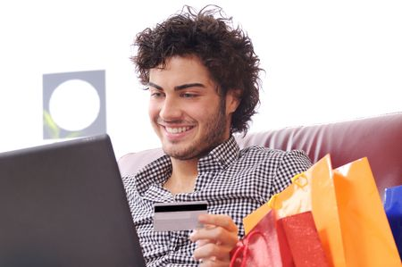 a young man  using his credit card to purchase over the internet, happiness and amazement photo