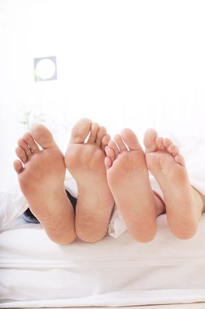 foots of two people in the bedroom, sleeping and relax on the white background Stock Photo