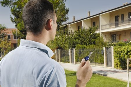 young man and new home; young man looking new home with door key in hand; concept of real estate