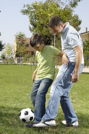 father and son playing football in urban park, concept of entertainment and education Stock Photo