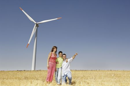Family and wind turbines; go for a walk between wind turnines; concept of ecology and alternative energy photo