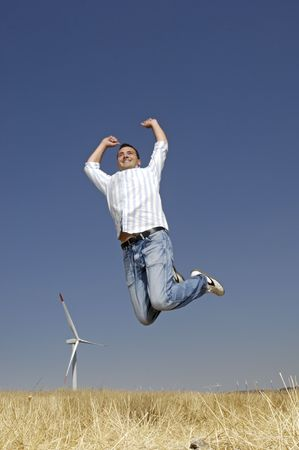 man and wind turbines; young adult jumping with wind turbines in background photo