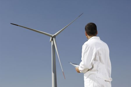 man and wind turbines; electronics engineer checking wind turbines, concept of alternative energy and ecology photo