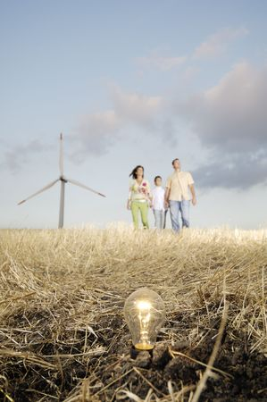 Family and wind turbines; go for a walk between wind turnines; light bulb in the ground, concept of ecology and alternative energy Stock Photo