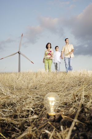 Family and wind turbines; go for a walk between wind turnines; light bulb in the ground, concept of ecology and alternative energy photo