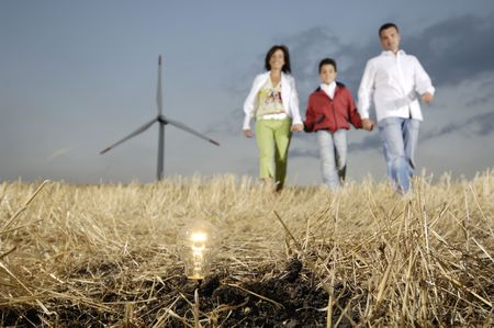Family and wind turbines; go for a walk between wind turnines; light bulb in the ground, concept of ecology and alternative energy Stock Photo - 4567972