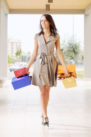 young woman with shopping bags, smiling and  walking