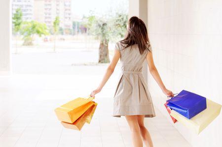 junge Frau mit Einkaufstaschen, lächelnd und Wandern Standard-Bild