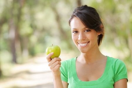 portrait of young woman with green apple, smiling and looking in camera