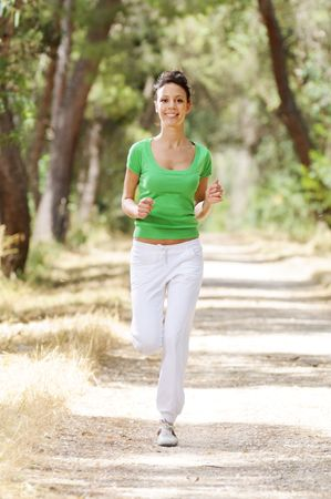 young woman running in green forest, smiling and looking in camera