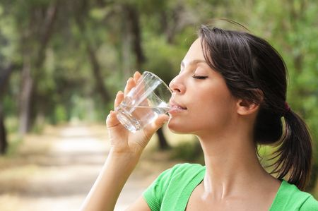 young woman drinking with water glass in green forest