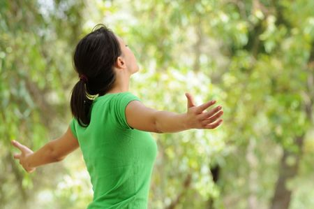 young woman in green forest, open arms and relax in vegetation