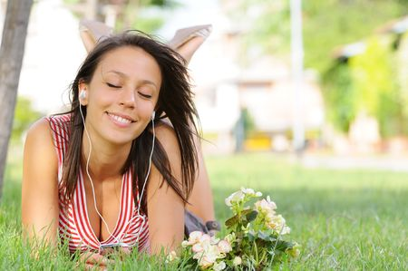 young woman listening music with headphones  in green park Stock Photo