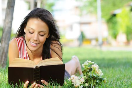 young woman reading book in green park