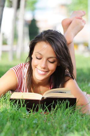 mujer leyendo libro: mujer joven en el libro de lectura parque verde