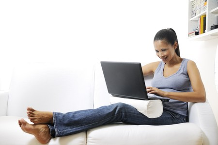 young woman smiling and using laptop at home with white background