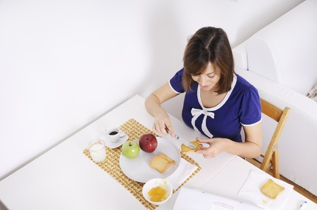 young woman in breakfast, eating and using laptop