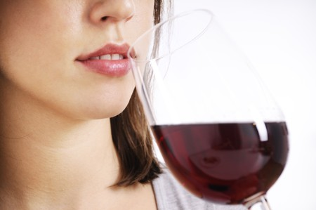 drinking glass: young woman drinking red wine on white background
