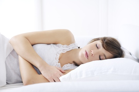 young woman sleeping on the bed with white background