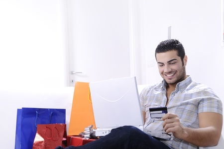 young man buying on internet with laptop in indoor Stock Photo - 9226189