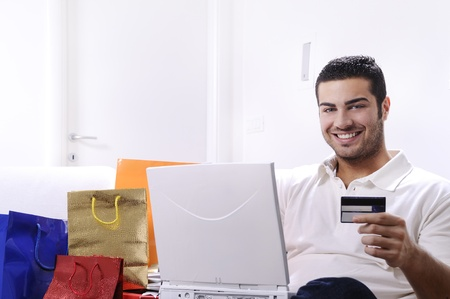 young man buying on internet with laptop in indoor Stock Photo - 9226204