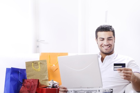 young man buying on internet with laptop in indoor Stock Photo - 9226188