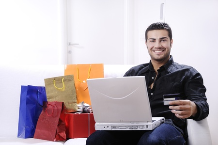 bugs shopping: young man buying on internet with laptop in indoor Stock Photo