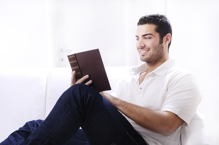 young man reading book in home interior on white background