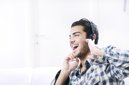 young man listening music in home interior on the white background Stock Photo