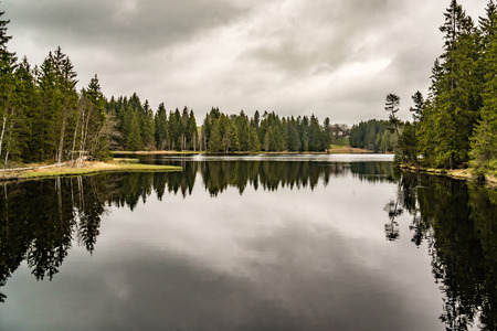 mystery lake with forest, dark water reflection cloudy Stock Photo