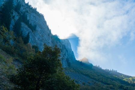 dramatic sun shining through clouds mountain view