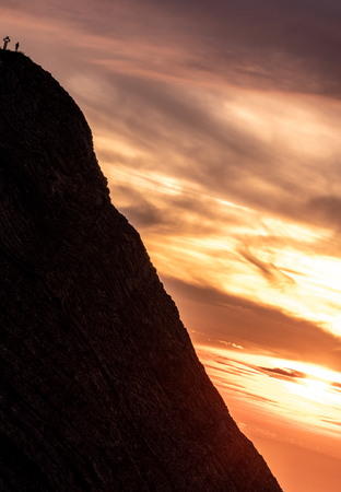 mountain peak with cross and people during sunset silhouette dramatic sunset brienzer rothorn switzerland alps