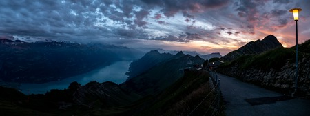 wide panorama view of mountain range during dramatic snuset from the brienzer rothorn in the swiss alps cloudy