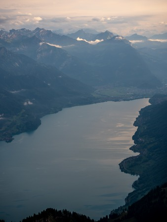 lake brienz seen from the brienzer rothorn, mountain lake during golden hour in the swiss alps cloudy