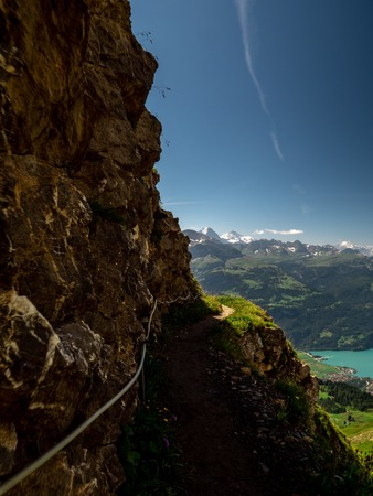mountain hiking path alongside steep mountain ridge with scenic view over the swiss alps brienzer rothorn