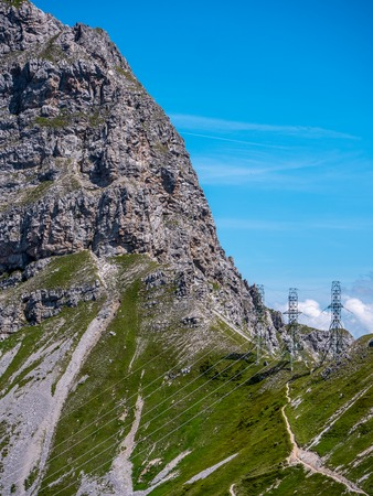 three high voltage post power poles high up in the mountains high voltage tower switzerland alps sunny