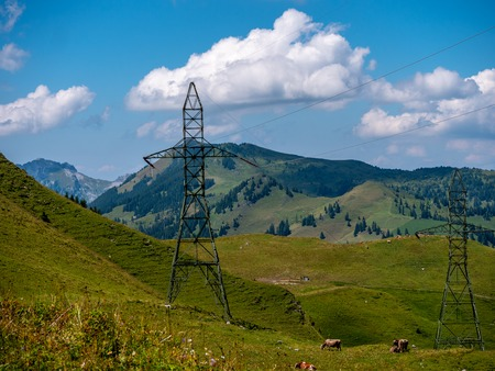 high voltage post power poles high up in the mountains high voltage tower switzerland alps sunny