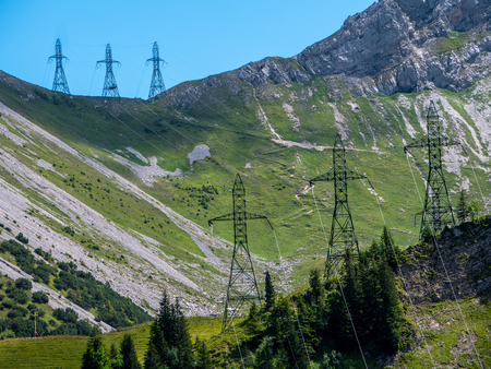 three high voltage post power poles in the mountains steep high voltage tower switzerland alps sunny