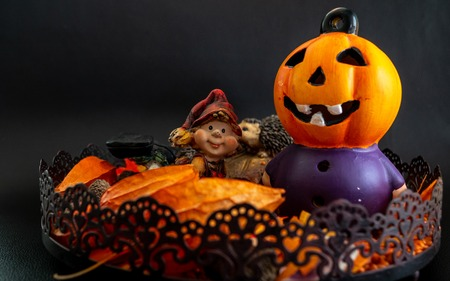 halloween autumn decoration with cute little dwarf and pumpkin head orange colors on black background Archivio Fotografico