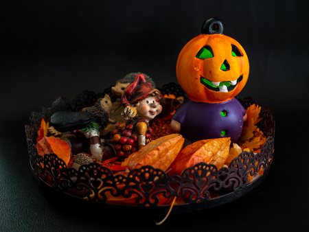 halloween autumn decoration with cute little dwarf and illuminated pumpkin head orange colors on black background fall