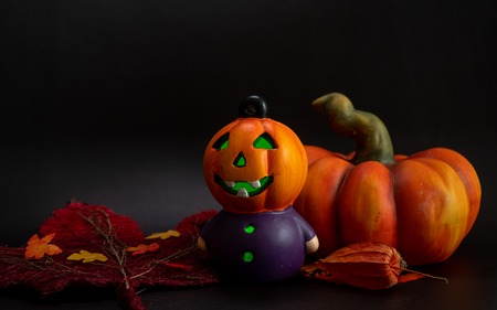 halloween autumn decoration with cute little dwarf and illuminated pumpkin head orange colors on black background fall studio