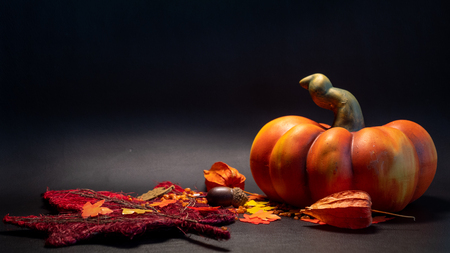 autumn fall decoration scene with artificial pumpkin leaves in orange color on black background studio