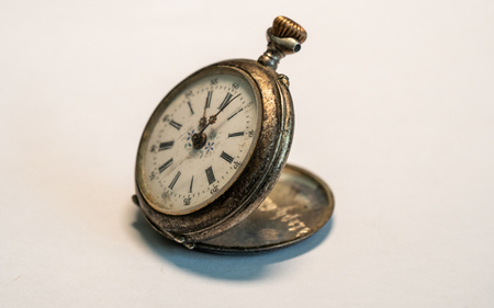 antique vintage pocket watch very old small watch rusty on white background studio light Archivio Fotografico