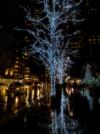 tree covered in white christmas lights reflecting on the rainy ground in new york during christmas rain reflections Archivio Fotografico