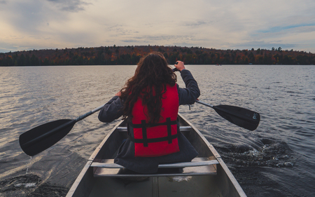 two girls canoeing with silver canoe on lake in canada algonquin national park on a sunny cloudy day during fall