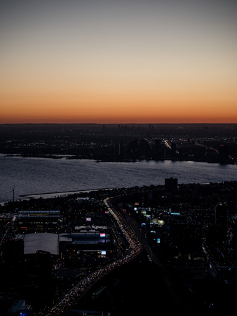 vertical view from cn tower to toronto downtown during dawn sunset with highway and traffic jam, canada