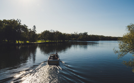 boat from behind driving on a beautiful river in a park during sunny summer day on toronto island lak ontario Archivio Fotografico
