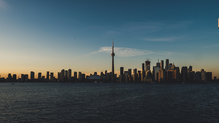 toronto skyline during sunset seen from toronto island with lake ontario infront dawn
