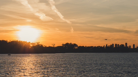plane tacking off into sunset with lake infront beautiful scene with soft orange color background toronto airport