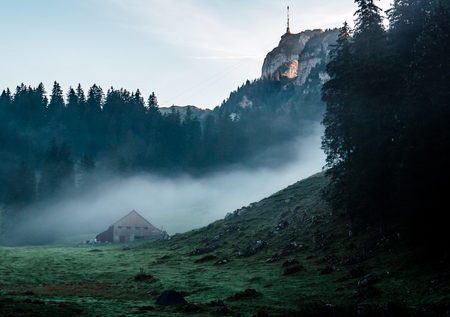mysterious mountain hut and tent during morning sunrise with fog, switzerland Archivio Fotografico - 120999295